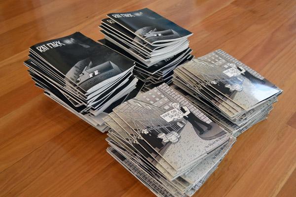 Four piles of Stuart McMillen comic books from crowdfunding drive: War on Drugs and Rat Park.