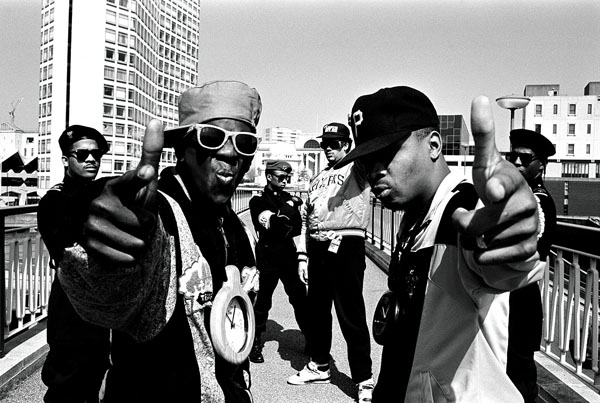 Public Enemy black and white photo. Flavor Flav and Chuck D on a bridge posing.