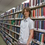 Stuart McMillen standing between library shelves - colour, wide shot.