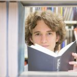Stuart McMillen in a library, looking between books on a book shelf, holding a book in his hands. Colour.