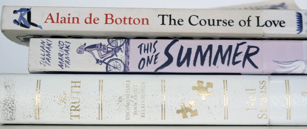 "Book spines: Alain de Botton ""The Course of Love"", Jillian Tamaki and Mariko Tamaki ""This One Summer"", Neil Strauss ""The Truth"""