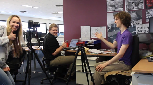 Interns helping with video shoot in coworking office. Standing behind a DSLR video camera tripod on film set.