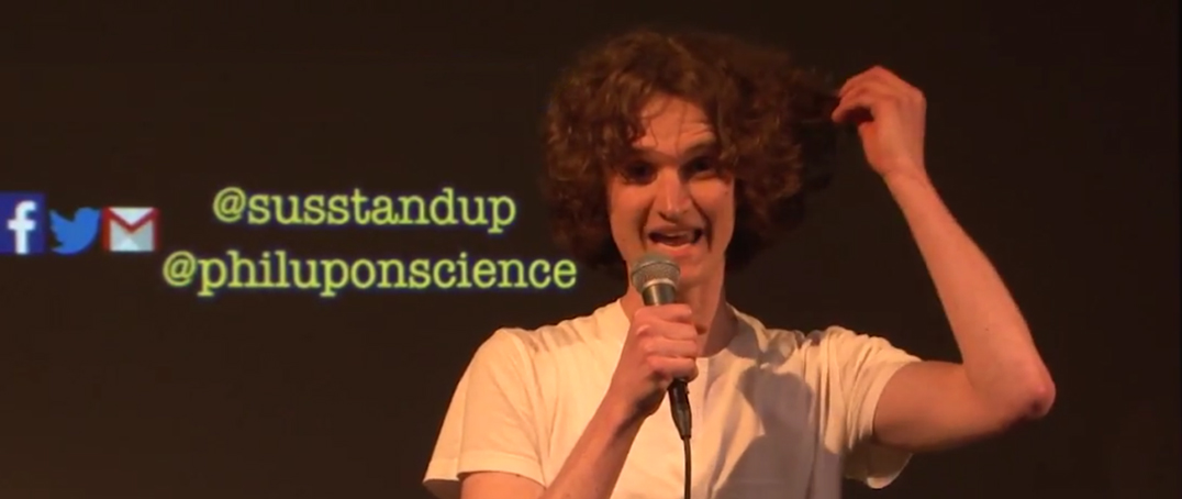 Stuart McMillen holding microphone performing stand up comedy