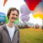 Cartoonist Stuart McMillen in 2018, standing in front of colourful hot air balloons, smiling at camera.