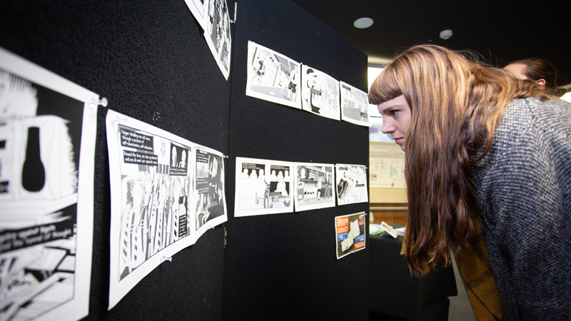Side view of young woman looking closely at artwork on wall display