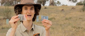 Stuart McMillen crowdfunding video wearing Akubra hat, holding money