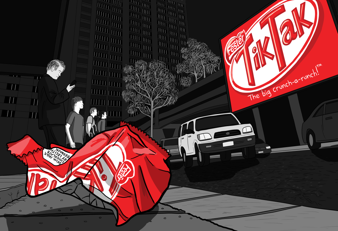Littered Kit Kat chocolate wrapper in a gutter next to a downtown street, with large billboard ad across the road.