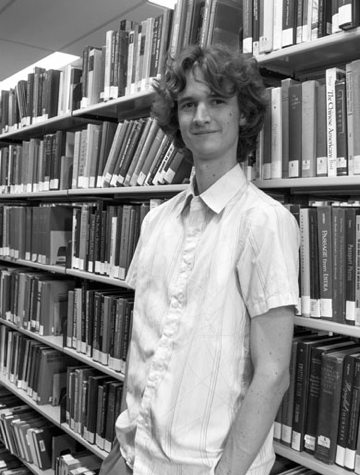 Black and white photograph of Australian cartoonist Stuart McMillen. Standing in front of a book shelf in a library.