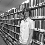 Stuart McMillen standing between library shelves - black and white, wide shot.