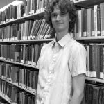 Stuart McMillen standing between library shelves - black and white, mid shot.