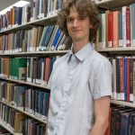 Stuart McMillen standing between library shelves - colour, mid shot.