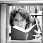 Stuart McMillen in a library, looking between books on a book shelf, holding a book in his hands. Black and white.