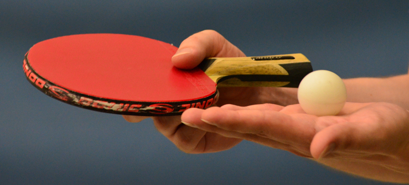 Table tennis racket and ball in hands