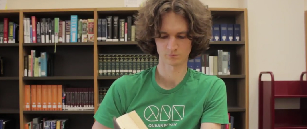 Stuart McMillen in green shirt, reading a book in the National Library of Australia