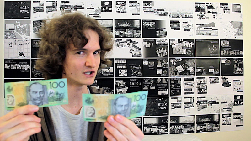 Stuart McMillen crowdfunding video holding two $100 notes