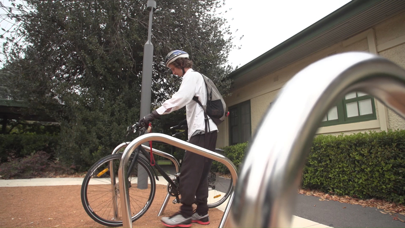 Low angle view of Stuart McMillen parking bike at bicycle racks.