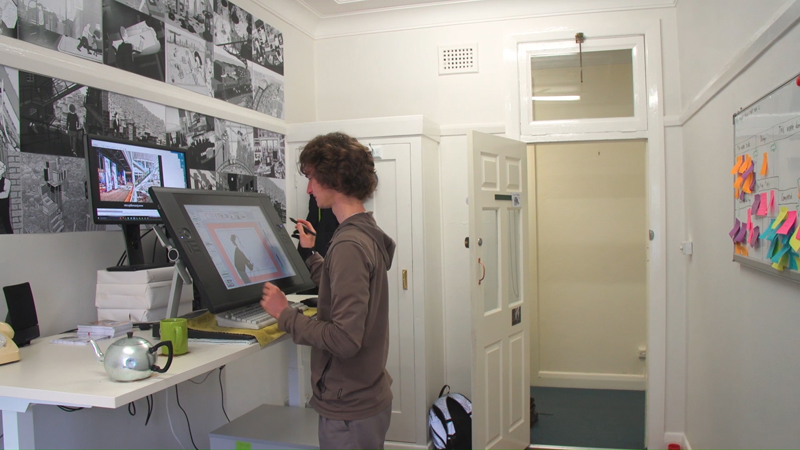 View of Stuart McMillen working at standing desk in Gorman Arts Centre art studio office.
