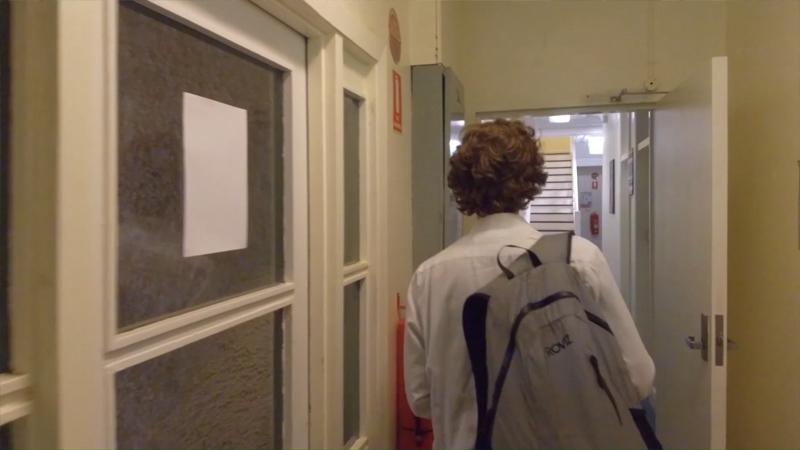 Rear view of Stuart McMillen wearing backpack walking down the hallway.