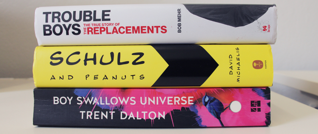 "Spines of books: ""Trouble Boys"" by Bob Mehr, ""Schulz and Peanuts"" by David Michaelis, and ""Boy Swallows Universe"" by Trent Dalton"