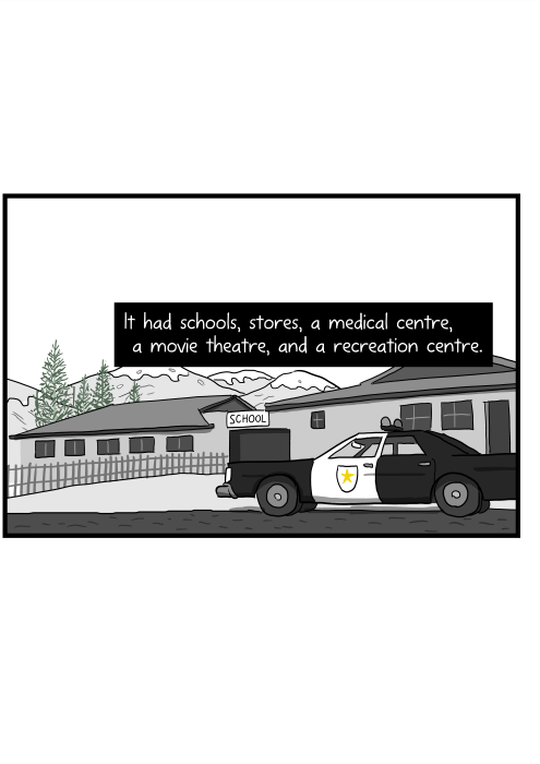 It had schools, stores, a medical centre, a movie theatre, and a recreation centre. Cartoon of police car parked outside small town building.