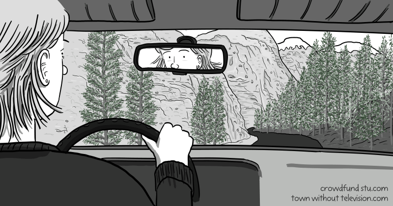 View from back seat of a car, showing a female driver holding the steering wheel, driving the car down a mountain road.